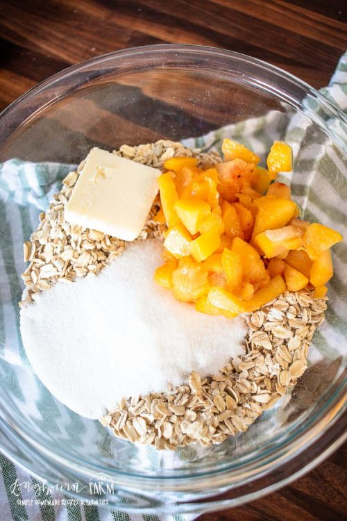 a bowl full of oats peaches sugar and butter