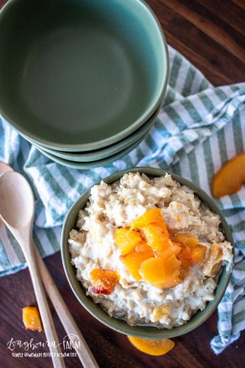 a serving bowl full of peaches and cream oatmel topped with chopped fresh peaches