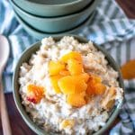 a serving bowl full of peaches and cream oatmeal topped with chopped fresh peaches