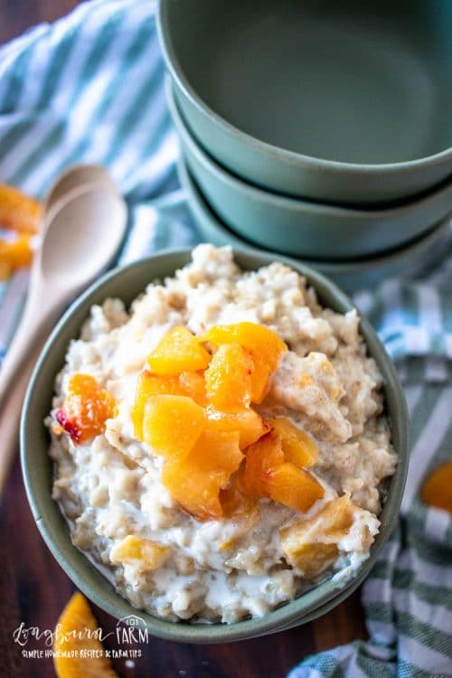 peaches and cream oatmeal in a bowl topped with fresh pieces and empty bowls to the side
