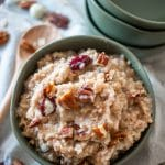pecan oatmeal in a serving bowl topped with chopped pecans and empty bowls to the side