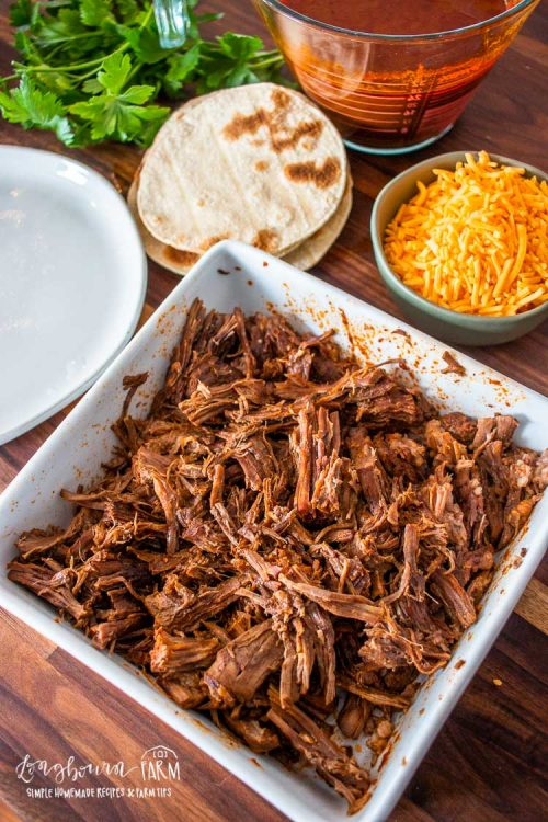 shredded beef in a square bowl with tortillas and cheese in the background
