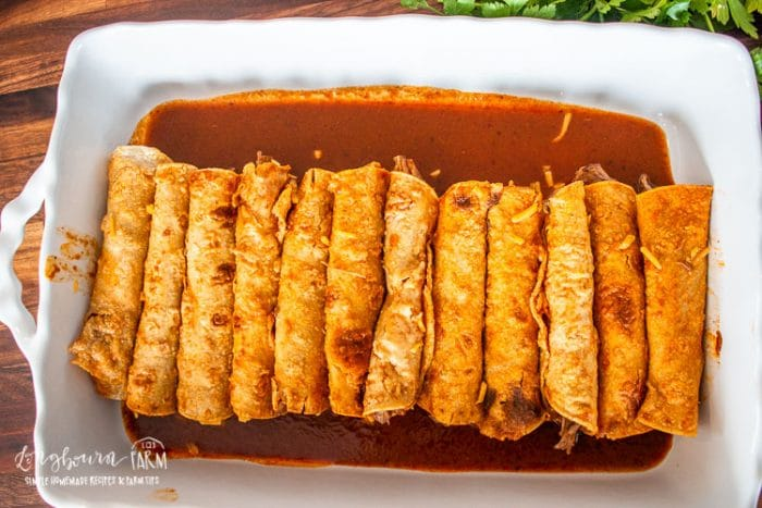 a baking dish filled with shredded beef enchiladas and sauce