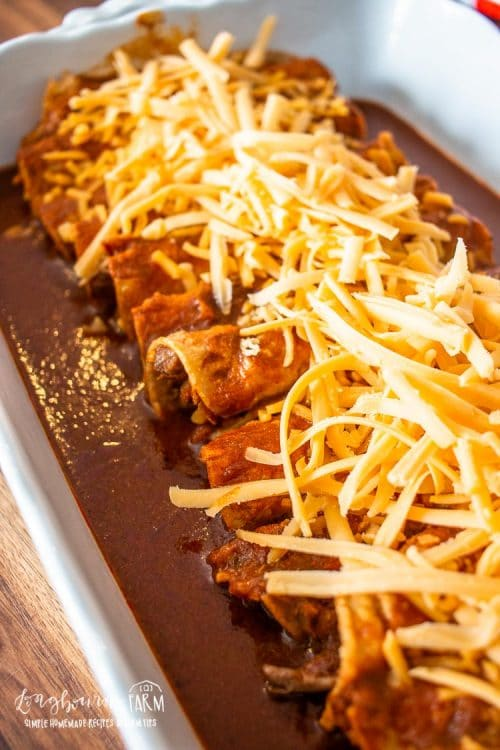a baking dish filled with shredded beef enchiladas and sauce topped with cheeses