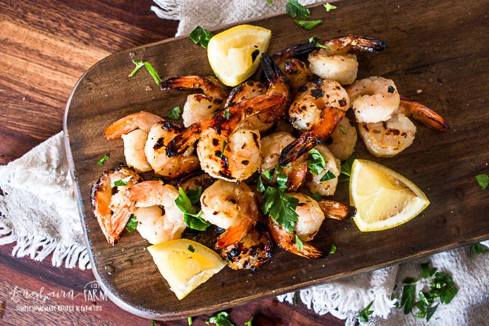 an aerial view of honey garlic shrimp on a wooden cutting board with garnishes