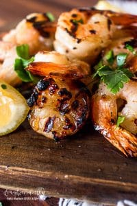 a close up view of honey garlic shrimp on a wooden cutting board with garnishes
