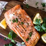 salmon fillet on a cutting board with garnishes