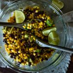 avocado corn salad in a bowl with wooden spoons and lime wedges