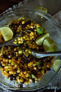 lime wedges and wooden spoons in a glass bowl full of black beans, corn, and avocado sald