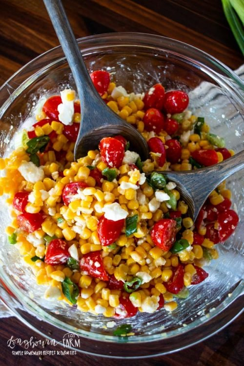 two wooden spoons in the corn tomato salad