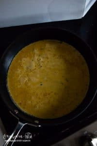a skillet full of cooking omelet