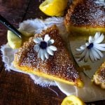 a removed slice of lemon tart with flower on top and squeezed lemons to the sides