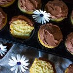 yellow cupcakes with chocolate frosting in muffin tray with fresh flowers