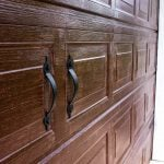 up close view of garage door with gel stain and black handles added