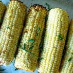 chives on grilled corn on the cob on a platter