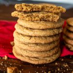 a stack of brown sugar cookies with the top cookie broken in half to reveal soft inside