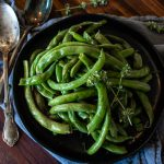 a bowl of green beans with fresh herbs next to two spoons