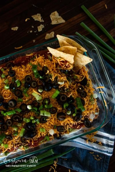 a glass baking dish filled with 7 layer taco dip and a stack of tortilla chips in the corner