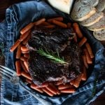 an aerial view of a chuck roast on a plate surrounded by cooked baby carrots and a sliced loaf of bread to the side