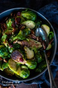a large metal spoon in a bowl of roasted brussel sprouts with pecans