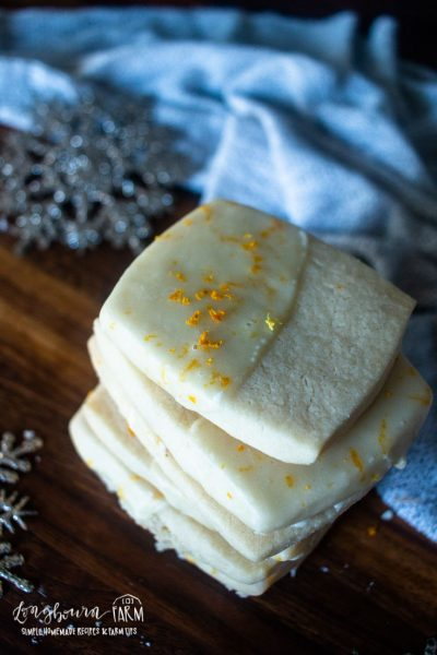 square shaped orange zest topped orange shortbread cookies next to snowflakes and a blue towel
