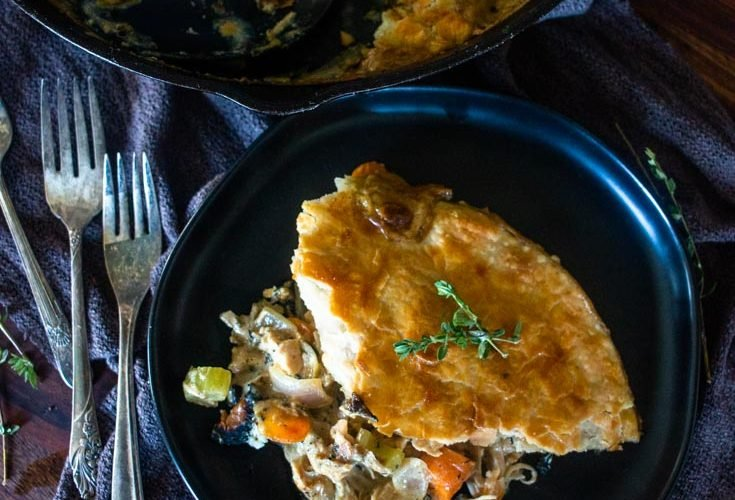 a serving of skillet pot pie on a plate with more in a skillet to the side