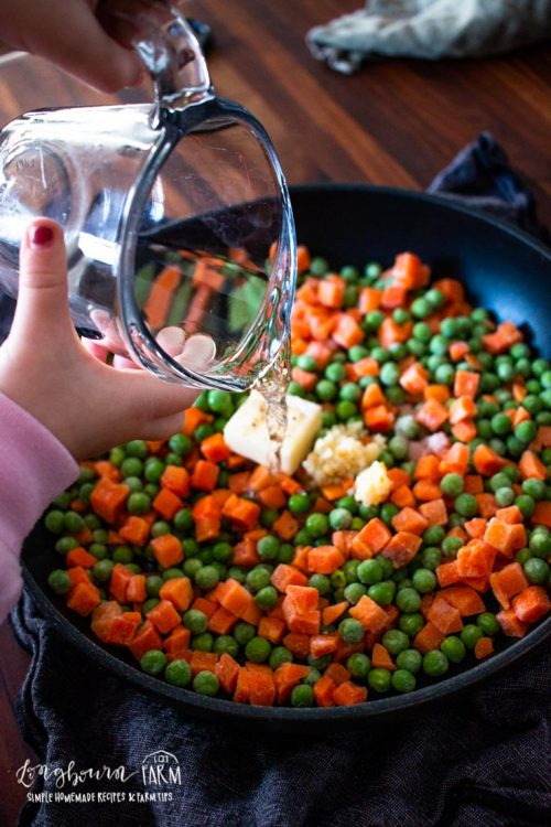 adding water to the skillet of frozen peas with butter and garlic
