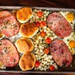 a sheet pan filled with diced potatoes, ham slices, eggs, and biscuits