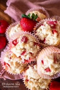 an upclose view of a stack of strawberry shortcake muffins with fresh strawberries