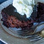crock pot chocolate lava cake on a plate with forks and whipped topping