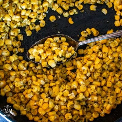an upclose aerial view of a skillet full of cooked corn with a large metal spoon resting inside