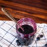 a jar full of homemade blueberry syrup with a spoon in it and fresh blueberries scattered around