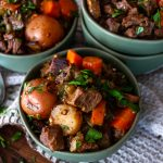 several blue bowls filled ith irish beef stew and topped with fresh chopped herbs