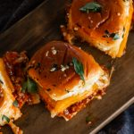 bbq beef sliders scattered on a wooden board