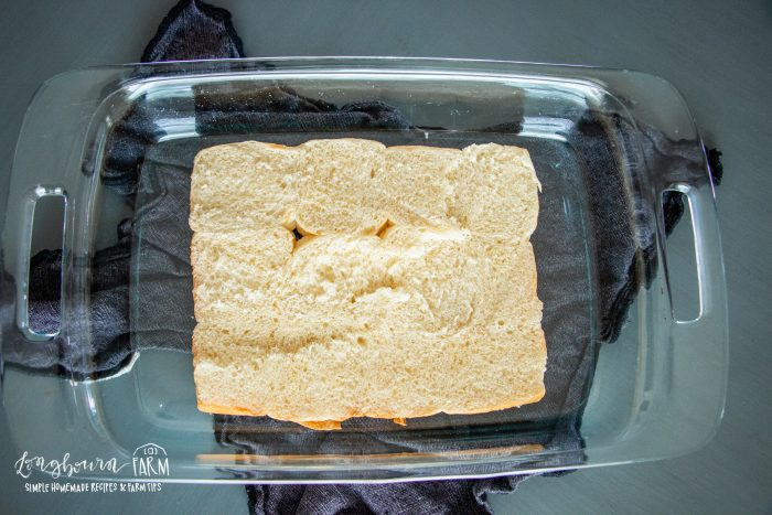 a aking dish with half a package of dinner rolls resting at the bottom