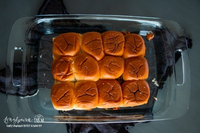 arranged and unbaked bbq beef dinner sliders in a glass baking dish