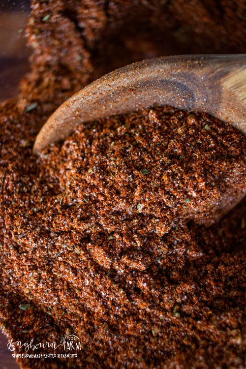an upclose view of taco seasoning in a bowl with a wooden spoon
