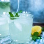 a side view of mint lemonade in glass cups with ice and a mint leaf garnish