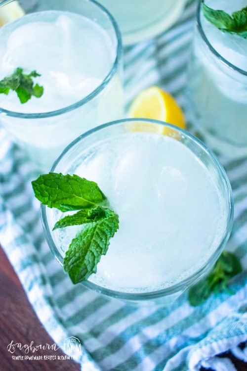 mint lemonade in glass cups with mint leaves on the sides for garnish