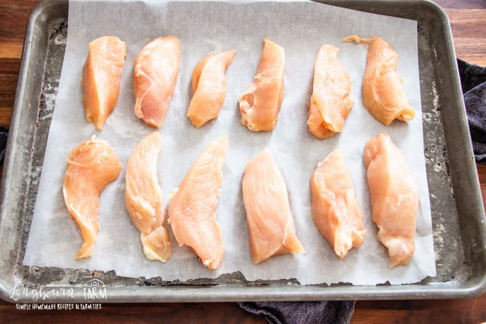 raw chicken pieces on a lined baking sheet