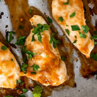 herb topped baked teryiak chicken breasts on a parchment paper lined baking sheet