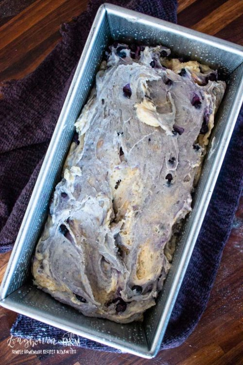 a bread pan filled with blueberry banana bread batter